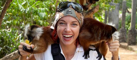 smiling backpacker girl holding a monkey
