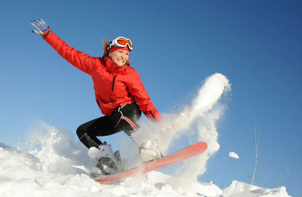 Woman snowboarding in the morning