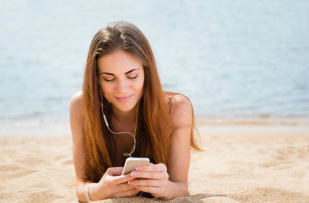 Woman using phone on beach