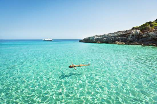 woman relaxing on air mattress on clear sea water in menorca best beaches