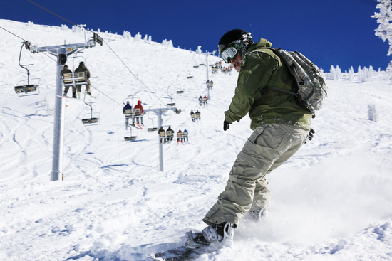 man snowboarding in ski resort area Utah USA