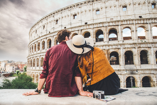 couple of tourists enjoying the view of Colosseum in Rome Italy