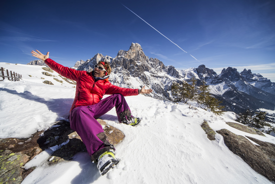ski girl sitting on the rocks in Passo Rolle, Dolomites, Italy