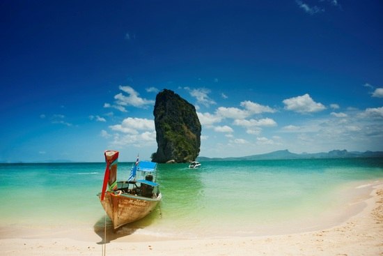 A long-tail boat is anchored on a Thailand beach
