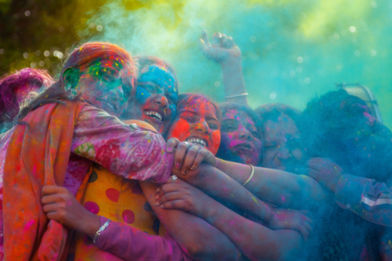 Group of friends covered in bright colouful powder celebrating Holi in India