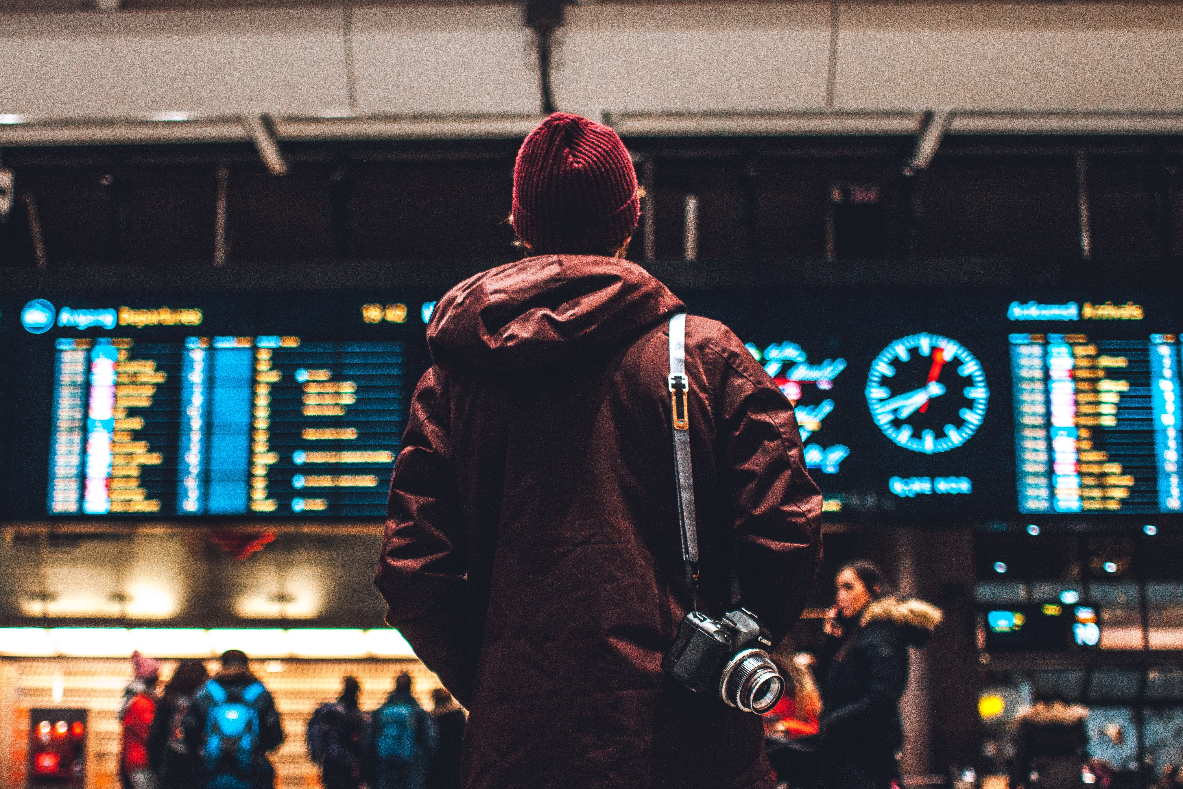 man looking up at a departure board at an airport