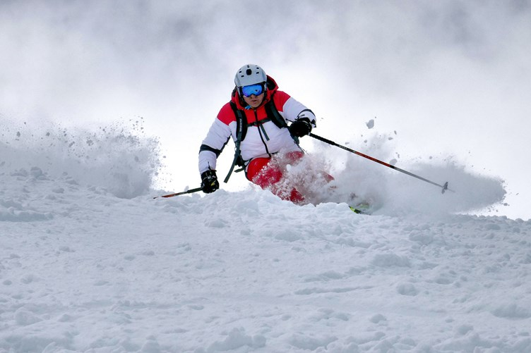 Skieer going through snow in pila, aosta valley, italy