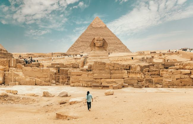 Man walking up to the Sphinx and Pyramids in Egypt