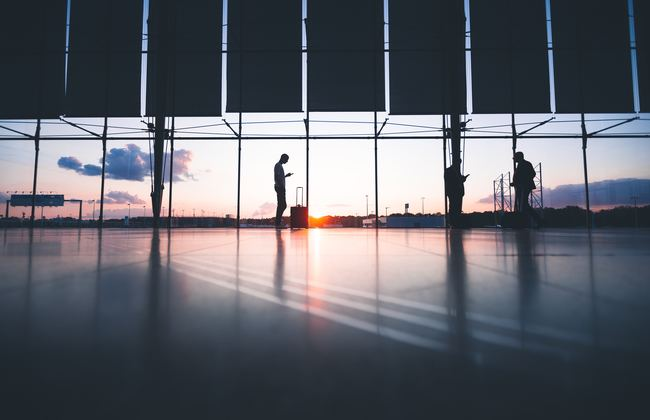 Three people standing in an airport as the sun rises in the distance