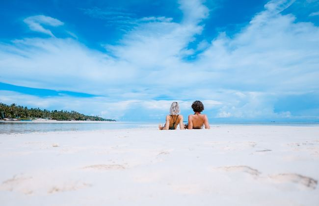 Two people laying together on a sandy beach looking at a cloudy blue sky