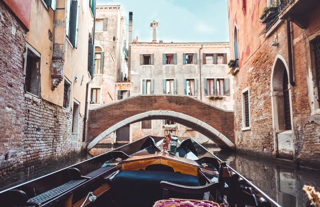 Gondola point of view in front of a bridge on canal in Venice, Italy