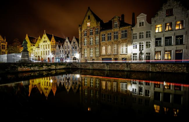 View of lake and buildings at night in Bruges, Belgium