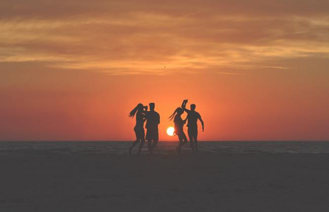 Friends standing on a beach in front of a sunset