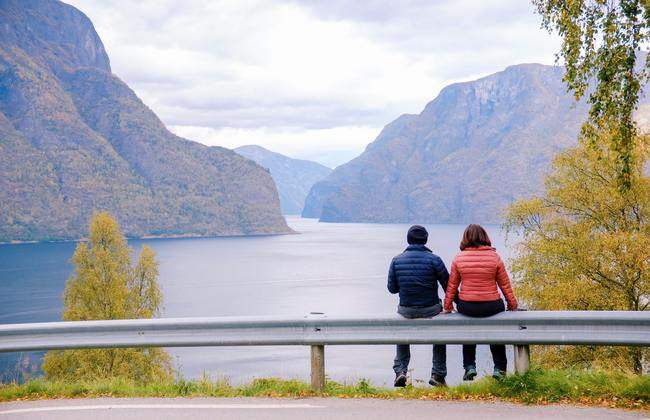 Couple sitting together, looking at a lake and hills