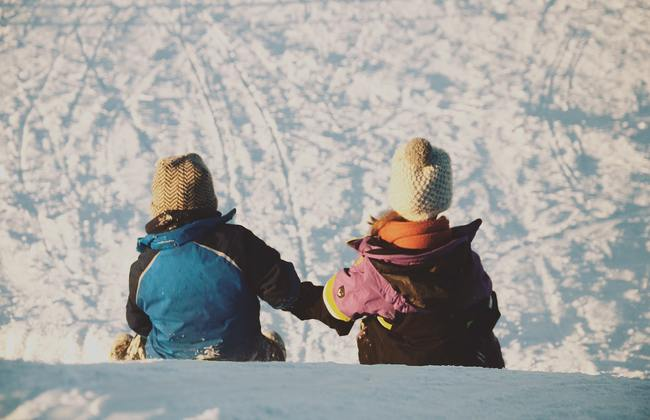 Two children holding hands as they sledge down a snowy hill